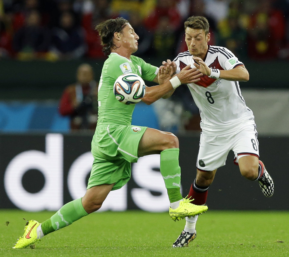 Photo - Algeria's Mehdi Mostefa, left, pushes off Germany's Mesut Ozil to stop his attack during the World Cup round of 16 soccer match between Germany and Algeria at the Estadio Beira-Rio in Porto Alegre, Brazil, Monday, June 30, 2014. (AP Photo/Kirsty Wigglesworth)