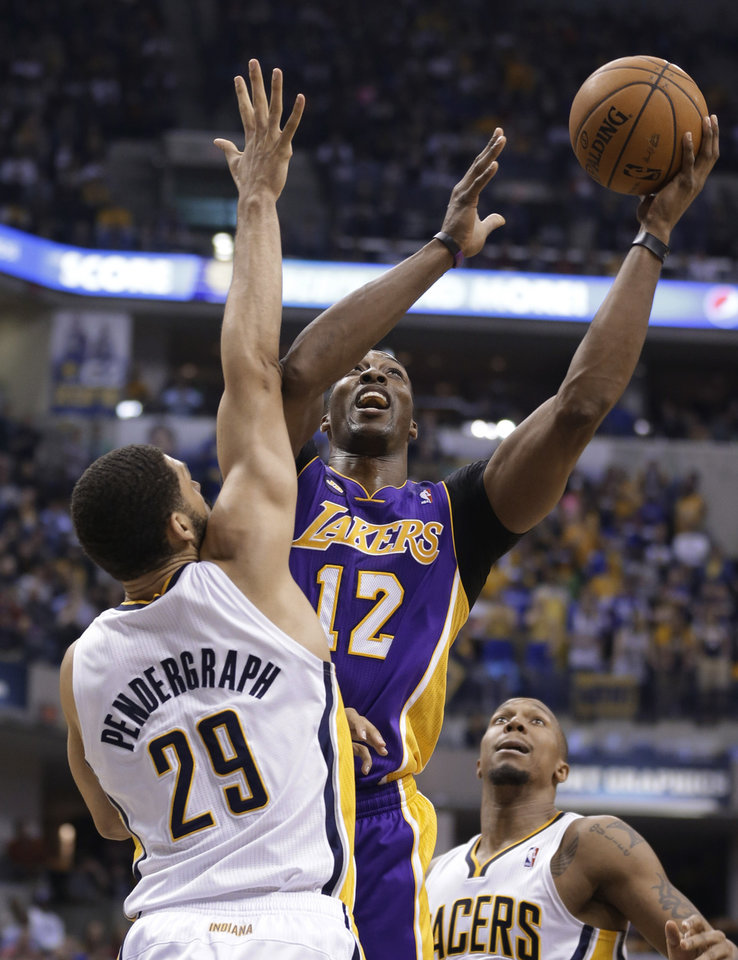 Photo - Los Angeles Lakers center Dwight Howard, right, hits a shot over Indiana Pacers forward Jeff Pendergraph in the first half of an NBA basketball game in Indianapolis, Friday, March 15, 2013. (AP Photo/Michael Conroy)
