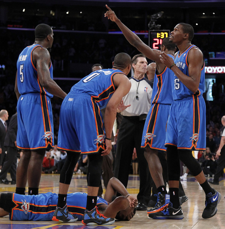 CORRECTS SPELLING OF NAME TO METTA, NOT META - Oklahoma City Thunder players stand over teammate James Harden, lower left, after receiving a flagrant double foul from Los Angeles Lakers\' Metta World Peace, who was then ejected, in the first half of an NBA basketball game, Sunday, April 22, 2012, in Los Angeles. (AP Photo/Reed Saxon) ORG XMIT: LAS102
