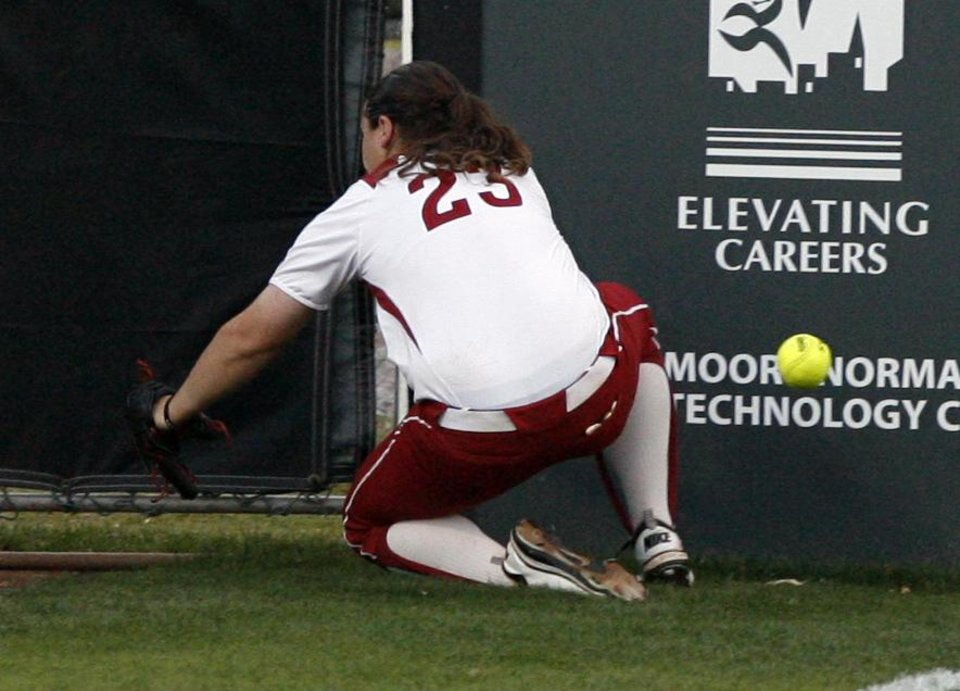 Sooner Brittany Williams tries but misses a ball hit foul to left field as the University of Oklahoma (OU) Sooners play the Oklahoma State University Cowgirls in NCAA college softball at Marita Hines Field on Wednesday, April 25, 2012, in Norman, Okla. Williams hit the fence and was injured on the play.  Photo by Steve Sisney, The Oklahoman
