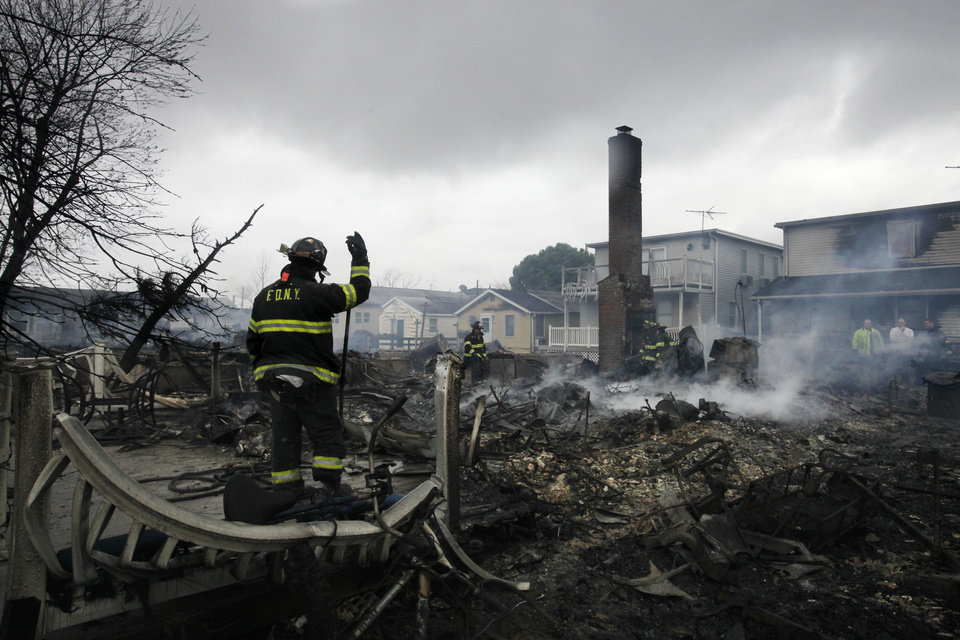 A fire fighter surveys the smoldering ruins of a house in the Breezy Point section of New York, Tuesday, Oct. 30, 2012. More than 50 homes were destroyed in a fire which swept through the oceanfront  community during superstorm Sandy. (AP Photo/Mark Lennihan) ORG XMIT: NYML111