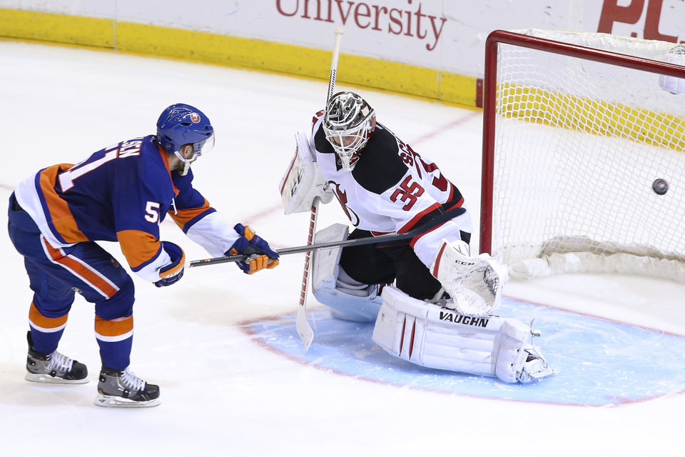 Photo - New York Islanders center Frans Nielsen (51) scores against New Jersey Devils goalie Cory Schneider (35) during a shootout of an NHL hockey game on Saturday, March 29, 2014, in Uniondale, N.Y. The Islanders defeated the Devils 2-1. (AP Photo/John Minchillo)