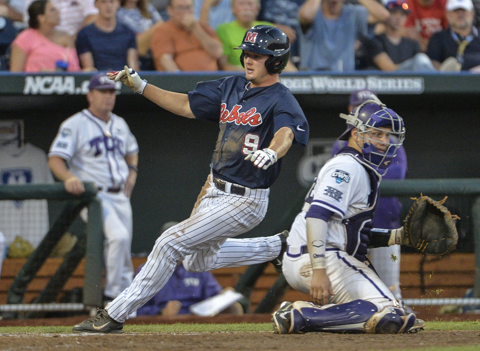 Photo - Mississippi's Auston Bousfield (9) runs past TCU catcher Kyle Bacak (6) on his way to score on a single by Sikes Orvis in the fifth inning of an NCAA baseball College World Series elimination game in Omaha, Neb., Thursday, June 19, 2014. (AP Photo/Ted Kirk)