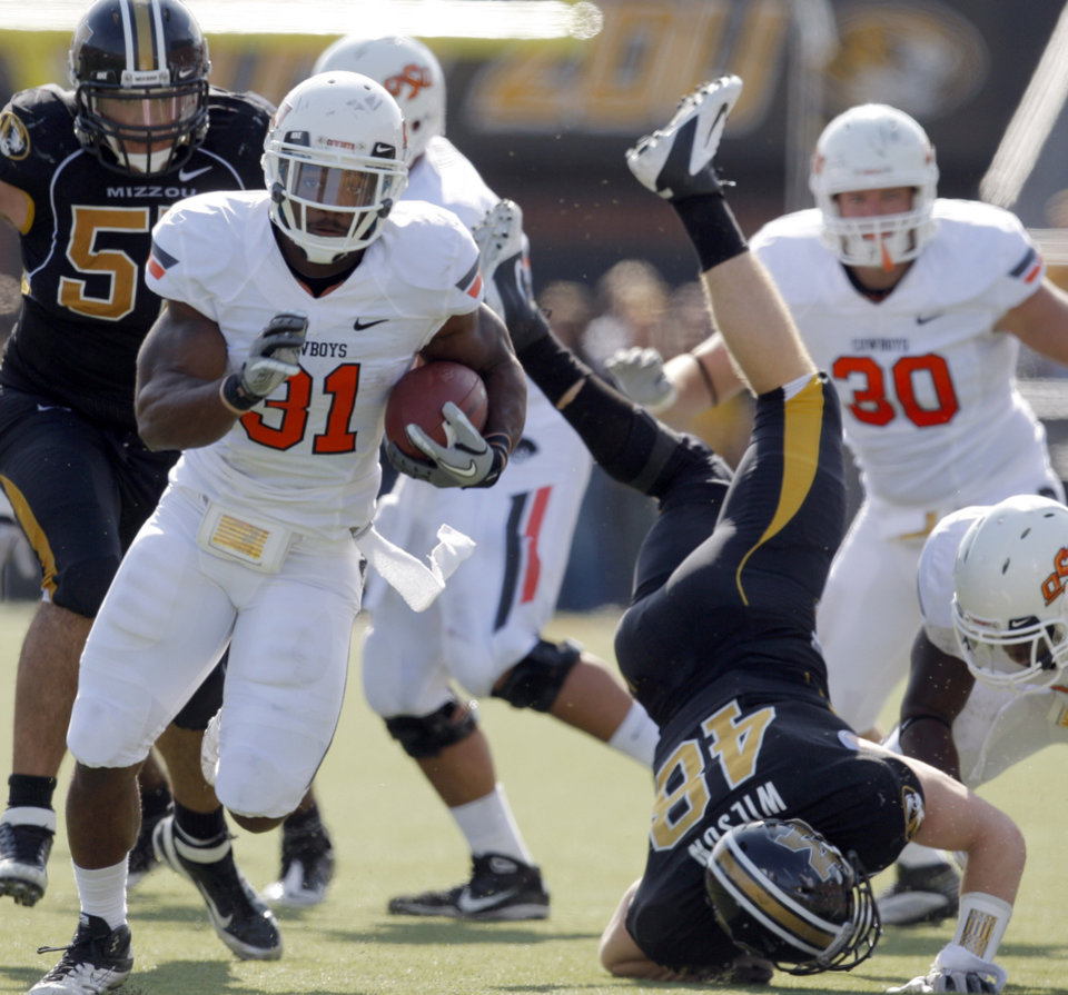 Photo - Oklahoma State's Jeremy Smith (31) runs up field as Missouri's Andrew Wilson (48) is up ended during a college football game between the Oklahoma State University Cowboys (OSU) and the University of Missouri Tigers (Mizzou) at Faurot Field in Columbia, Mo., Saturday, Oct. 22, 2011. Photo by Sarah Phipps, The Oklahoman
