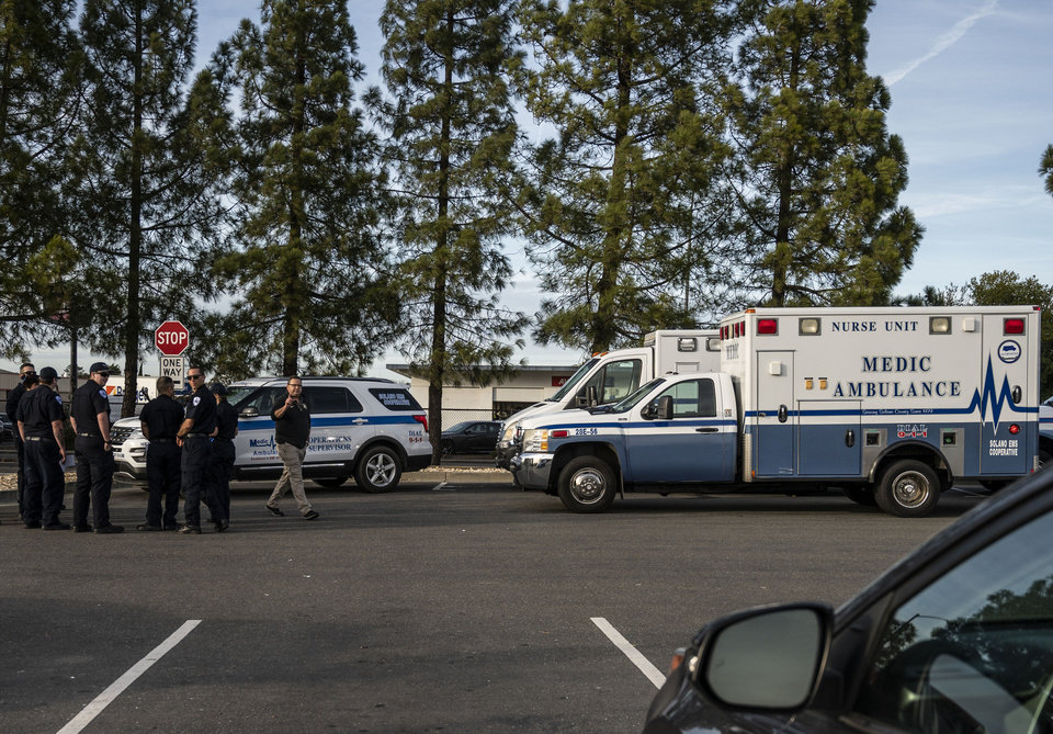 Photo -  A group of ambulances from the Solano EMS Cooperative stage at the visitor center at Travis Air Force Base, adjacent to Fairfield, Calif., Sunday, Feb. 16, 2020. A group of Americans cut short a 14-day quarantine on the Diamond Princess cruise ship in the port of Yokohama, near Tokyo, to be whisked back to America. But they will have to spend another quarantine period at U.S. military facilities including Travis to make sure they don't have the new virus that's been sweeping across Asia. (AP Photo/Hector Amezcua)