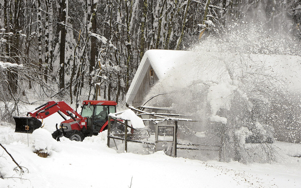 Photo -   Charles Blamble uses his heavy tractor to blow out the driveway of Jeff Coberly on Thursday afternoon, Nov. 1, 2012, in Aurora, W.Va. About 3 feet of snow is still on the ground in Aurora from this week's storm. (AP Photo/The Dominion Post, Ron Rittenhouse)