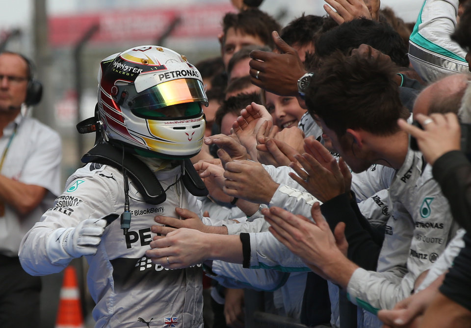Photo - Mercedes driver Lewis Hamilton of Britain, left, is congratulated by his team members after the Chinese Formula One Grand Prix at Shanghai International Circuit in Shanghai, Sunday, April 20, 2014. (AP Photo/Eugene Hoshiko)