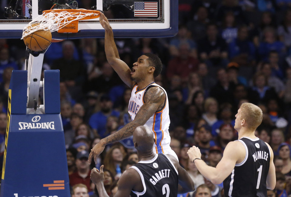 Oklahoma City Thunder forward Perry Jones (3) dunks in front of Brooklyn Nets center Kevin Garnett and forward Mason Plumlee (1) in the second quarter of an NBA basketball game in Oklahoma City, Thursday, Jan. 2, 2014. (AP Photo/Sue Ogrocki)