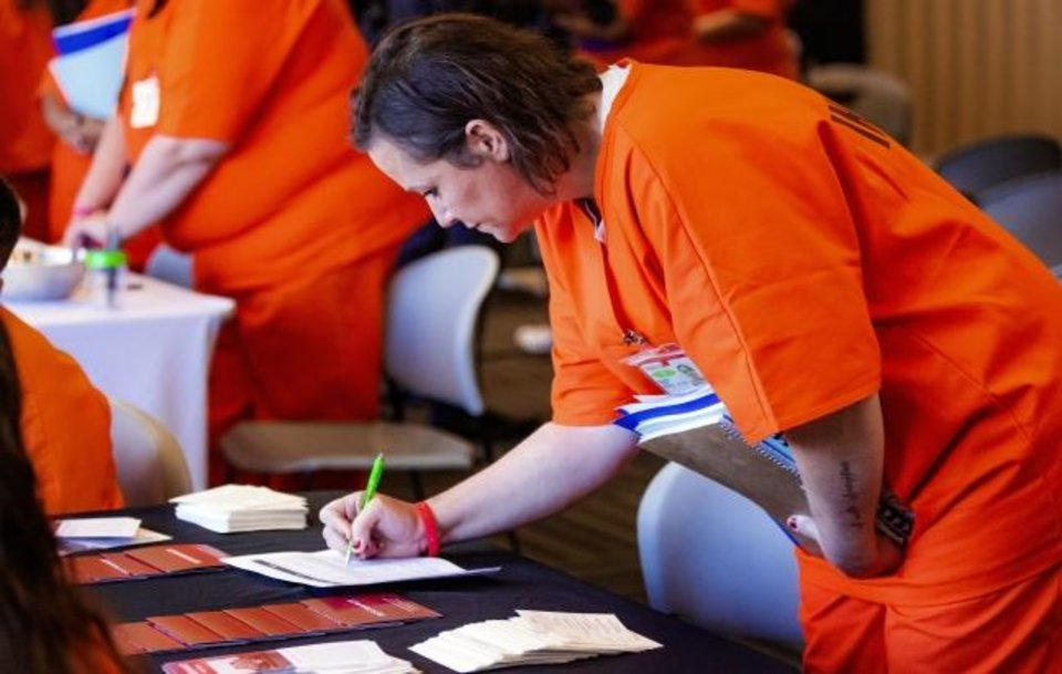 Photo -  Inmate Tammy Harris signs up to speak with a nonprofit organization during a Transition Fair at Kate Barnard Correctional Center in Oklahoma City on Monday. [Chris Landsberger/The Oklahoman]