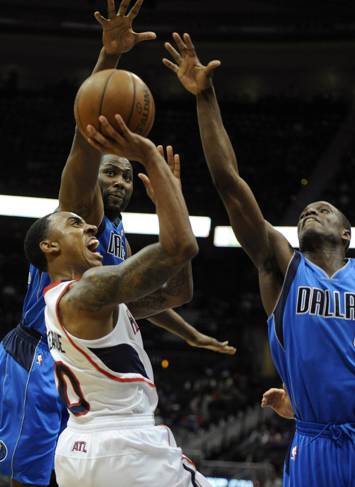 Photo - Atlanta Hawks guard Jeff Teague, left, shoots as Dallas Mavericks forward Elton Brand, and point guard Darren Collison, right, defend during the first half of an NBA basketball game, Monday, March 18, 2013, in Atlanta. (John Amis/AP Photo)