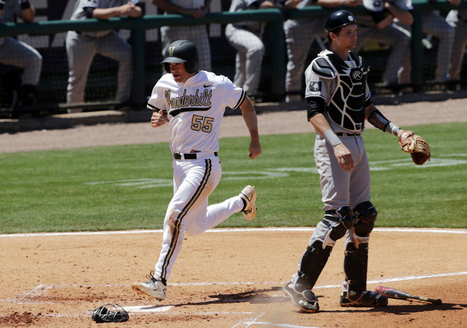 Photo - Vanderbilt's Conrad Gregor (55) scores on a throwing error by South Carolina pitcher Jordan Montgomery in the second inning as catcher Grayson Greiner watches during Southeastern Conference tournament college baseball game  at the Hoover Met in Hoover, Ala., Thursday, May 23, 2013. (AP Photo/Dave Martin)