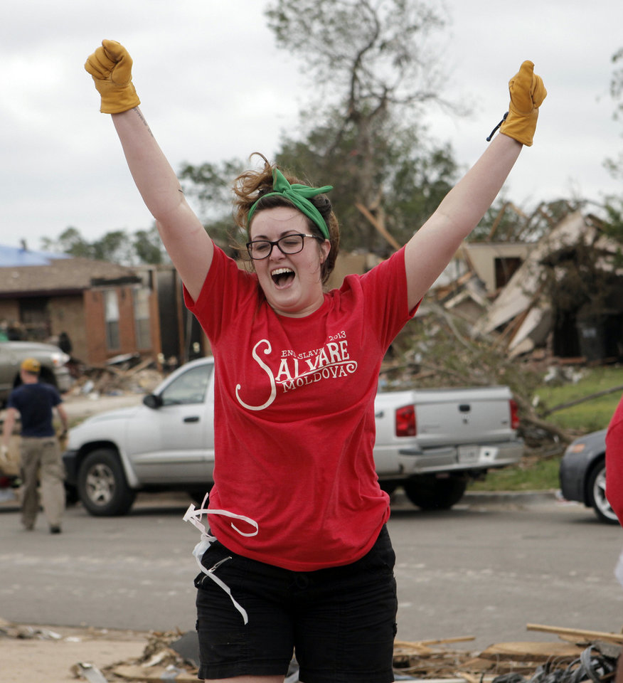 Photo - Krystal McKinney from Keller, Texas, cheers after her volunteer group removed a large shelving unit from a destroyed home in Moore on May 27, 2013. Photo by KT King, The Oklahoman