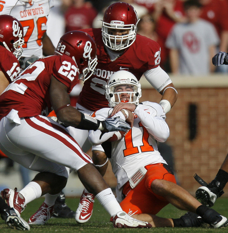 Photo - OSU's Zac Robinson is brought down by OU's Keenan Clayton, left, and Travis Lewis during the first half of the Bedlam college football game between the University of Oklahoma Sooners (OU) and the Oklahoma State University Cowboys (OSU) at the Gaylord Family-Oklahoma Memorial Stadium on Saturday, Nov. 28, 2009, in Norman, Okla.
