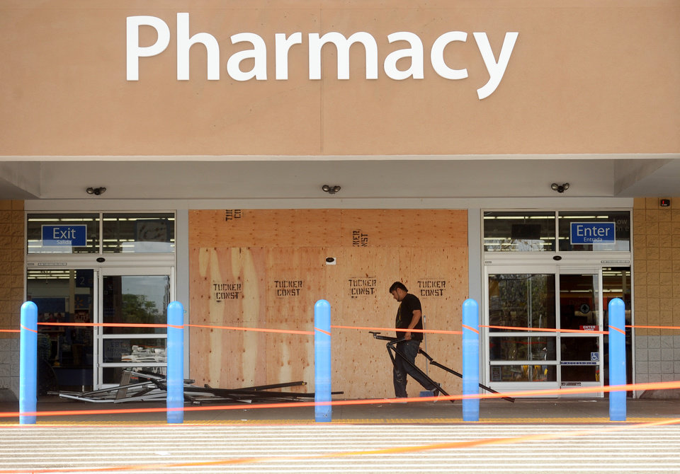 A worker cleans up damage at a Walmart in San Jose, Calif., after a motorist drove through a store entrance and began assaulting shoppers on Sunday, March 31, 2013. Four people sustained injuries during the attack according to a police spokesman. (AP Photo/Noah Berger)