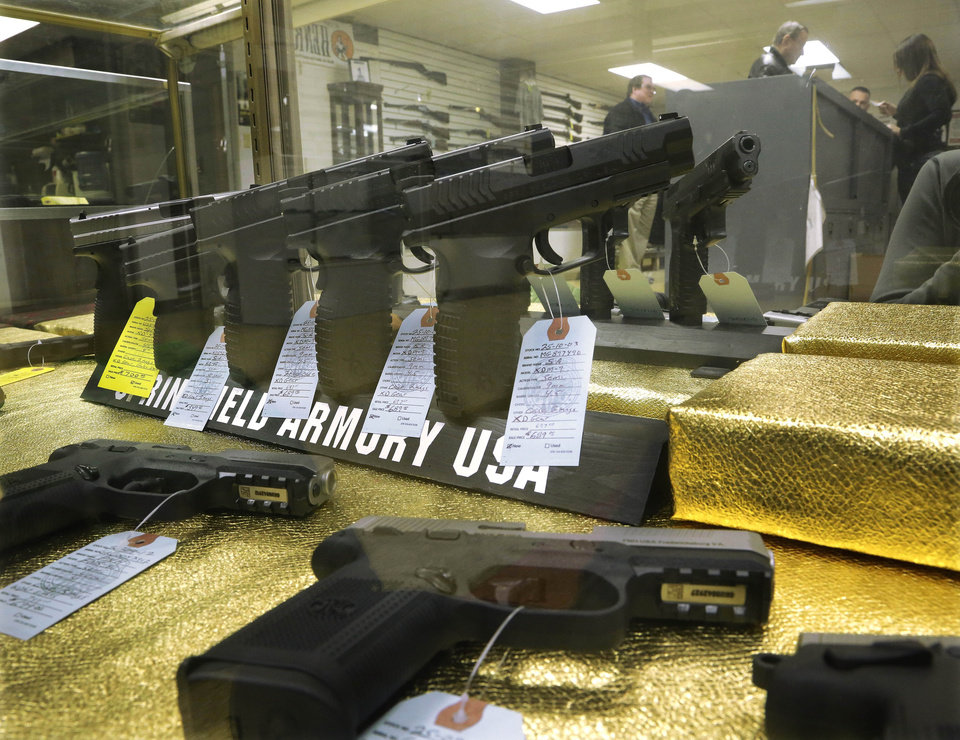 Photo - Hand guns are seen for sale at Capitol City Arms Supply Wednesday, Jan. 16, 2013 in Springfield, Ill. President Barack Obama launched the most sweeping effort to curb U.S. gun violence in nearly two decades, announcing a $500 million package that sets up a fight with Congress over bans on military-style assault weapons and high-capacity ammunition magazines just a month after a shooting in Connecticut killed 20 school children. (AP Photo/Seth Perlman)