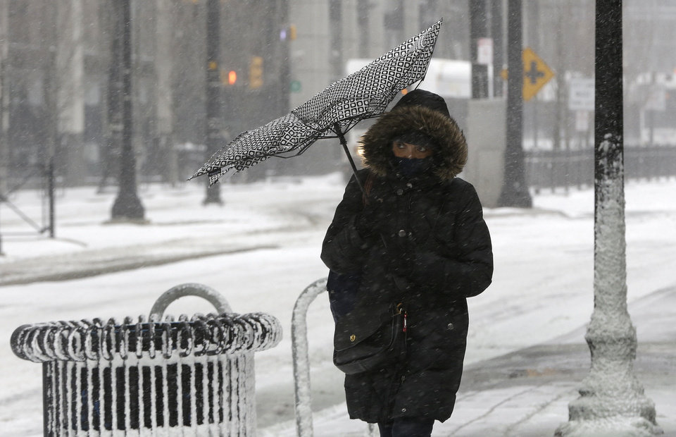Photo - Wind flips over the canopy of an umbrella as a woman walks in gusty wind during a winter storm, Tuesday, Jan. 21, 2014, in Jersey City, N.J. The National Weather Service said the storm could bring 8 to 12 inches of snow to Philadelphia and New York City, and more than a foot in Boston. Bitterly cold air with wind chills as low as 10 degrees below zero was forecast. (AP Photo/Julio Cortez)