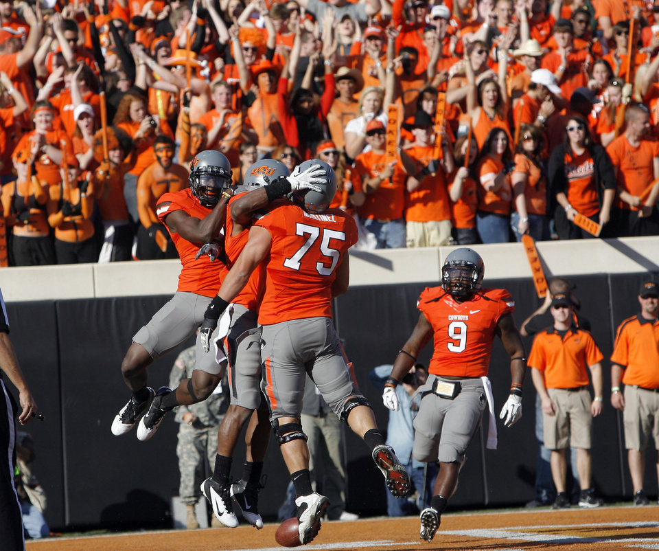 Photo - Oklahoma State players celebrate a Oklahoma State's Joseph Randle (1) touchdown during a college football game between the Oklahoma State University Cowboys (OSU) and the Baylor University Bears (BU) at Boone Pickens Stadium in Stillwater, Okla., Saturday, Oct. 29, 2011. Photo by Sarah Phipps, The Oklahoman