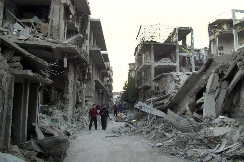 Photo - In this citizen journalism image provided by the Homs City Union of The Syrian Revolution, which has been authenticated based on its contents and other AP reporting,  Syrian citizens walk in a destroyed street that was attacked on Wednesday by Syrian forces warplanes, at Abu al-Hol street in Homs province, Syria, Thursday Nov. 29, 2012. Two US-based Internet-monitoring companies say Syria has shut off the Internet nationwide. Activists in Syria reached Thursday by satellite telephone confirmed the unprecedented blackout, which comes amid intense fighting in the capital, Damascus.(AP Photo/Homs City Union of The Syrian Revolution)