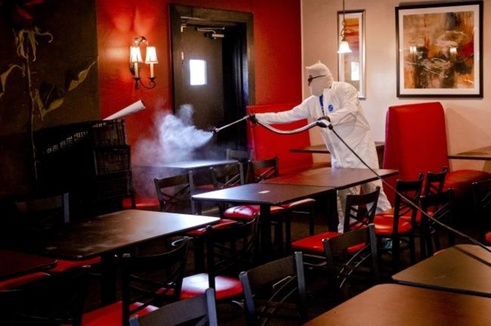 Photo -  Joe Barnes, owner of Safe Spray Services, sprays disinfectant at Rococo restaurant on Friday as he treats and cleans the surfaces.