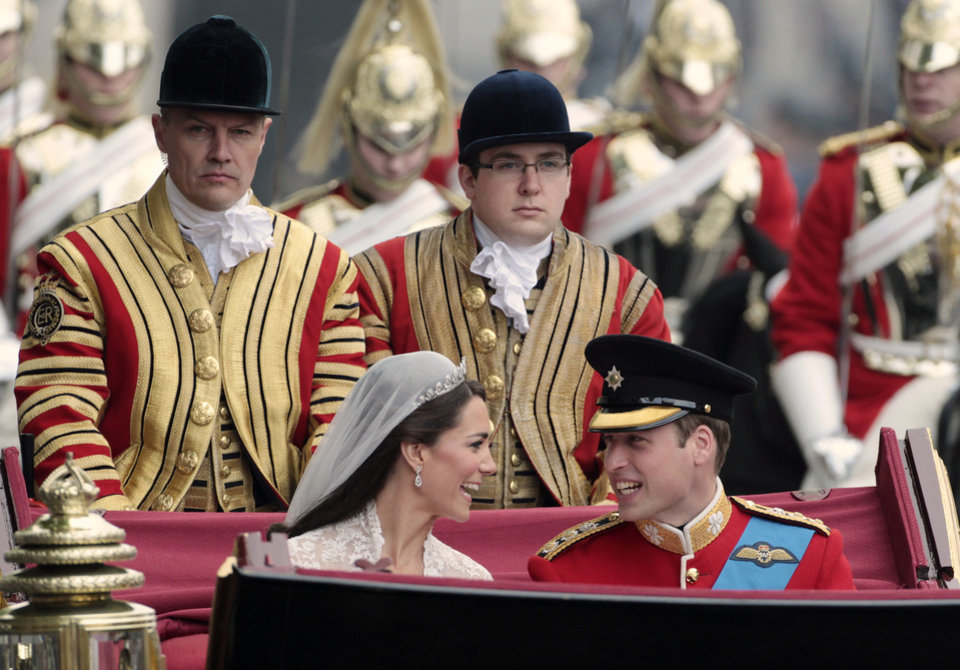 Photo - Britain's Prince William, front right, and his wife Kate, the Duchess of Cambridge, front left, make the journey by carriage procession to Buckingham Palace past crowds of spectators following their marriage at Westminster Abbey, London, Friday, April 29, 2011. (AP Photo/Matt Cardy, Pool) ORG XMIT: RWDA115