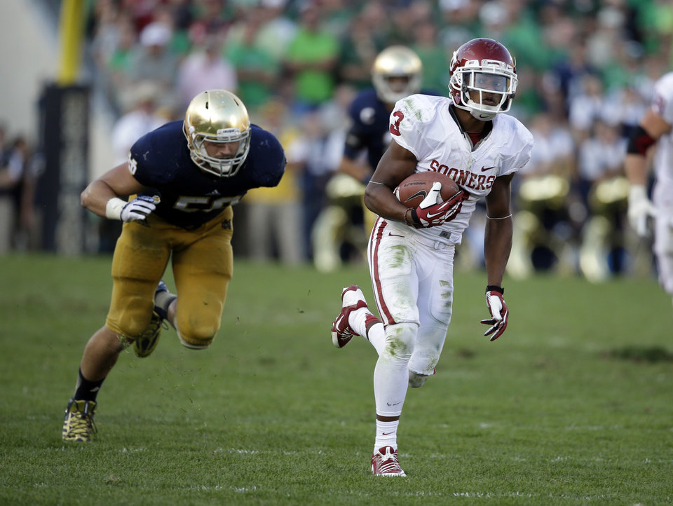 Oklahoma's Sterling Shepard (3) runs past Notre Dame's Jarrett Grace (59) for a 54-yard touchdown reception during the second half of an NCAA college football game on Saturday, Sept. 28, 2013, in South Bend, Ind. Oklahoma defeated Notre Dame 35-21. (AP Photo/Darron Cummings)  ORG XMIT: INDC116