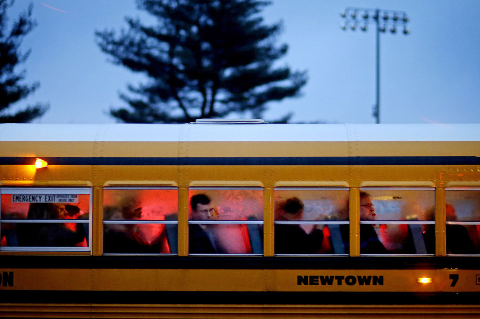 Photo - FILE - In this Dec. 16, 2012 file photo, people arrive on a school bus at Newtown High School for a memorial vigil attended by President Barack Obama for the victims of the Sandy Hook Elementary School shooting in Newtown, Conn. It was a year of storms, of raging winds and rising waters, but also broader turbulence that strained our moorings. 2012 battered us with floods and tempests, and seemed especially dark in its final days. (AP Photo/David Goldman, File)