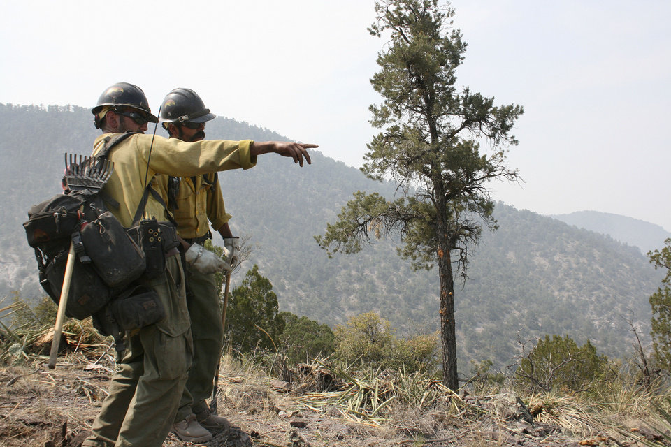 Photo -   Crew members from the Granite Mountain Hotshots of Prescott, Ariz., cut a fire line along a mountain ridge outside Mogollon, N.M., Saturday, June 2, 2012, in an effort to manage and contain the Whitewater-Baldy fire which has burned more than 354 square miles of the Gila National Forest in New Mexico. Unlike last year's megafires in New Mexico and Arizona, this blaze is burning in territory that has been frequently blackened under the watchful eye of the Gila's fire managers. (AP Photo/U.S. Forest Service, Tara Ross)