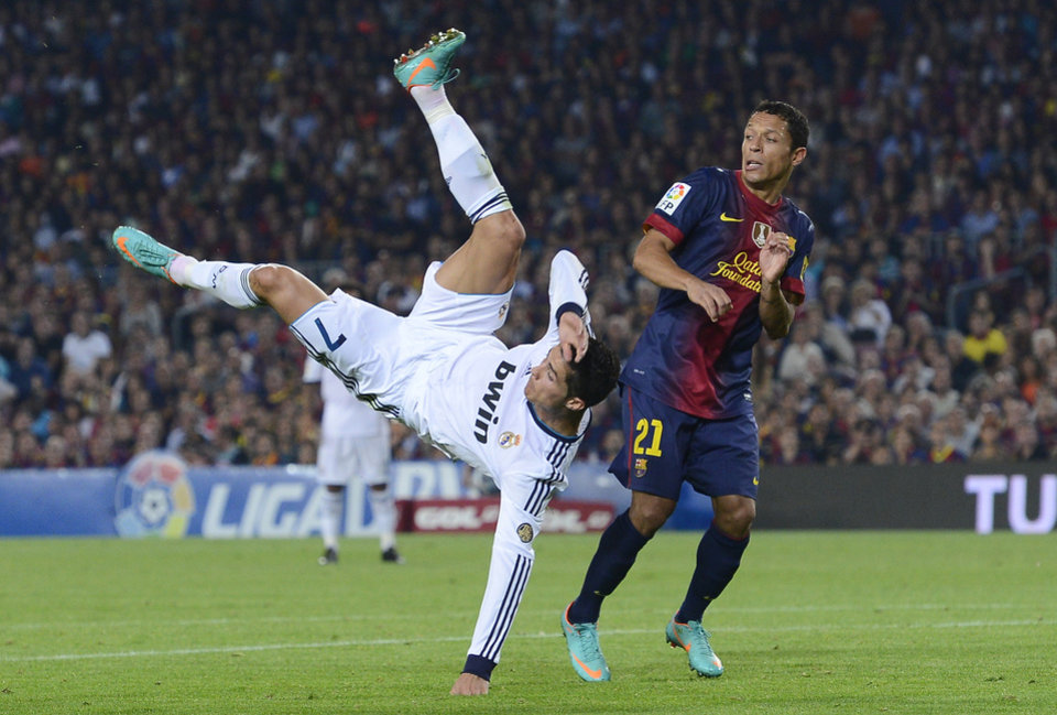 FC Barcelona's Adriano Correia from Brazil, right, duels for the ball against Real Madrid's Cristiano Ronaldo from Portugal during a Spanish La Liga soccer match at the Camp Nou stadium in Barcelona, Spain, Sunday, Oct. 7, 2012. (AP Photo/Manu Fernandez)