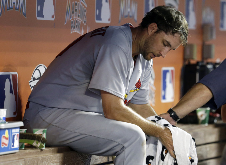 Photo - St. Louis Cardinals starting pitcher Adam Wainwright sits in the dugout after pitching in the fourth inning during a baseball game against the Miami Marlins, Tuesday, Aug. 12, 2014, in Miami. (AP Photo/Lynne Sladky)