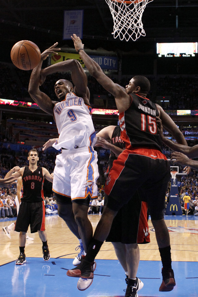 Photo - Oklahoma City's Serge Ibaka (9) tries to grab a rebound from Toronto's Amir Johnson (15) during the NBA basketball game between the Oklahoma City Thunder and the Toronto Raptors at Chesapeake Energy Arena in Oklahoma City, Sunday, April 8, 2012. Photo by Sarah Phipps, The Oklahoman.