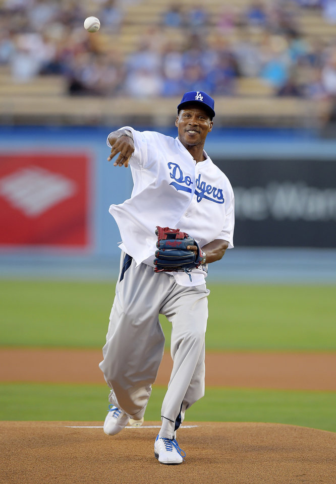 Photo - Los Angeles Lakers head coach Byron Scott throws out the ceremonial first pitch prior to a baseball game between the Los Angeles Dodgers and the Milwaukee Brewers, Friday, Aug. 15, 2014, in Los Angeles. (AP Photo/Mark J. Terrill)