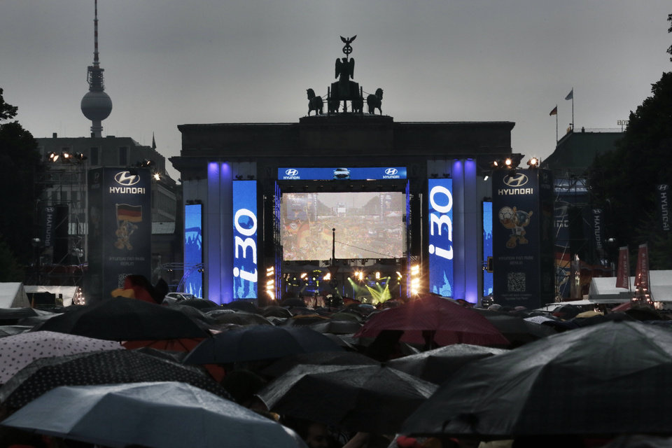 Photo - During heavy rain thousands of German soccer fans wait for the live broadcast of the final match  between Germany and Argentina of the soccer World Cup in Rio de Janeiro, Brazil,  at a public viewing area called 'Fan Mile' in front of the Brandenburg Gate in Berlin, Sunday, July 13, 2014. (AP Photo/Markus Schreiber)