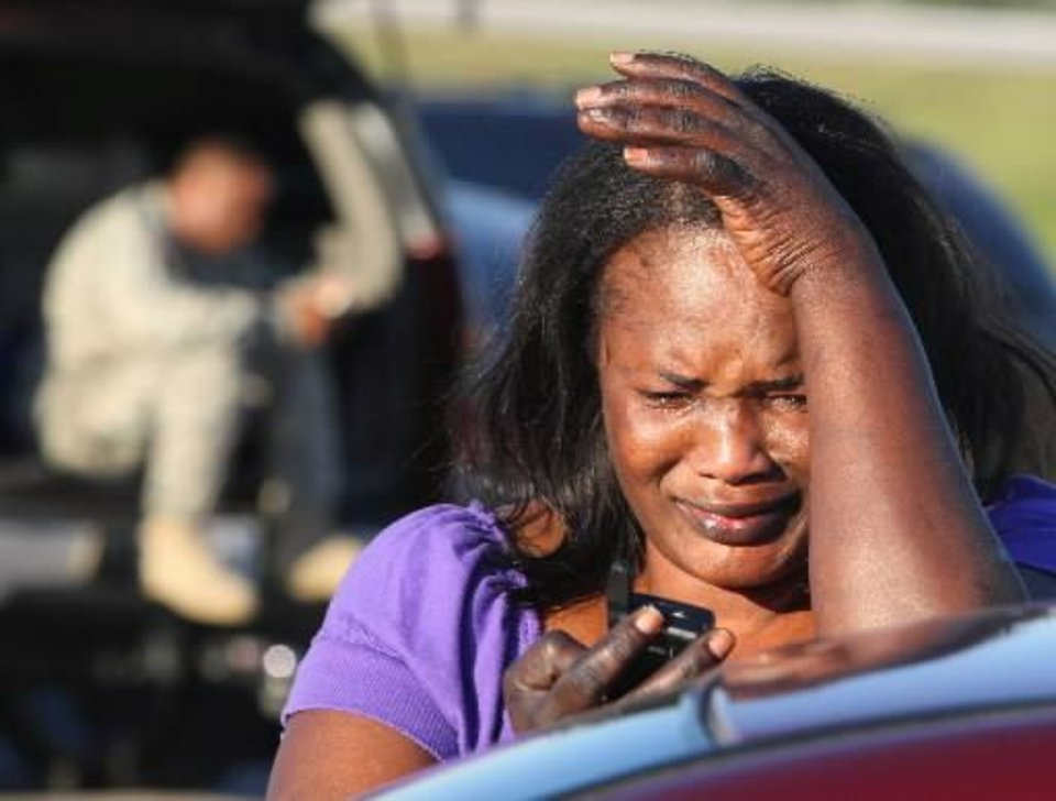Photo - Monica Cain, 44, wipes her eye as she tries to get in touch with her husband Sgt. Darren Cain who was stationed at  Fort  Hood, Texas, Thursday, Nov. 5, 2009. (AP Photo/Waco Tribune Herald, Jerry Larson)