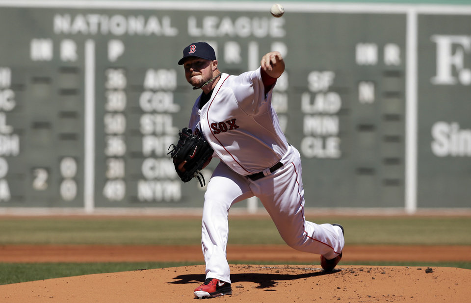 Photo - Boston Red Sox's Jon Lester delivers a pitch against the Milwaukee Brewers in the first inning of a baseball game Sunday, April 6, 2014, in Boston. (AP Photo/Steven Senne)