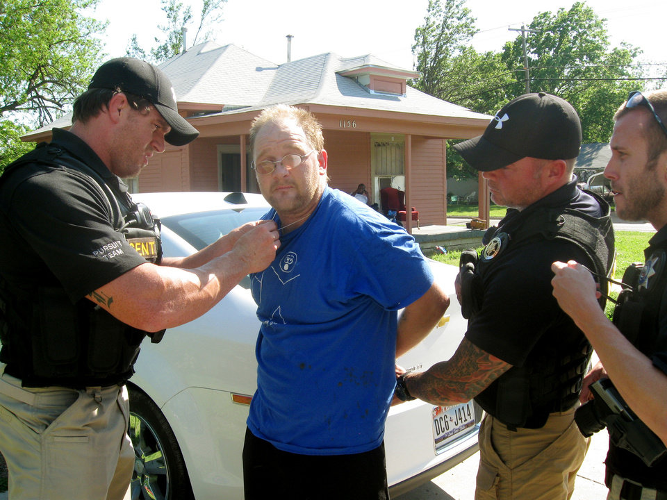 Bounty hunters Ryan Lopez, Mike Parsons and Eric London apprehend Wesley Baker, 36, who missed a court date in Oklahoma County and had several outstanding warrants. <strong>Matt Dinger</strong>
