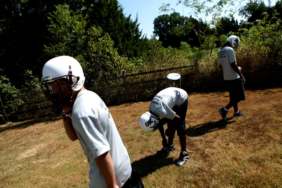 Photo - HIGH SCHOOL FOOTBALL: Three players rest between drills during football practice at Seeworth Academy  in Oklahoma City on Wednesday, August 25, 2010. The team practices in a yard on the southeast side of the Seeworth campus. Ten days before the first game, only seven players showed up for practice. Photo by John Clanton, The Oklahoman ORG XMIT: KOD