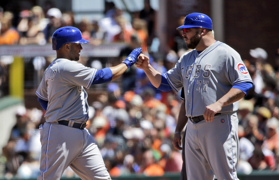 Photo - Chicago Cubs' Welington Castillo, left, is high fived by first base coach Eric Hinske after Castillo's RBI single against the San Francisco Giants during the sixth inning of a baseball game on Monday, May 26, 2014, in San Francisco. (AP Photo/Marcio Jose Sanchez)