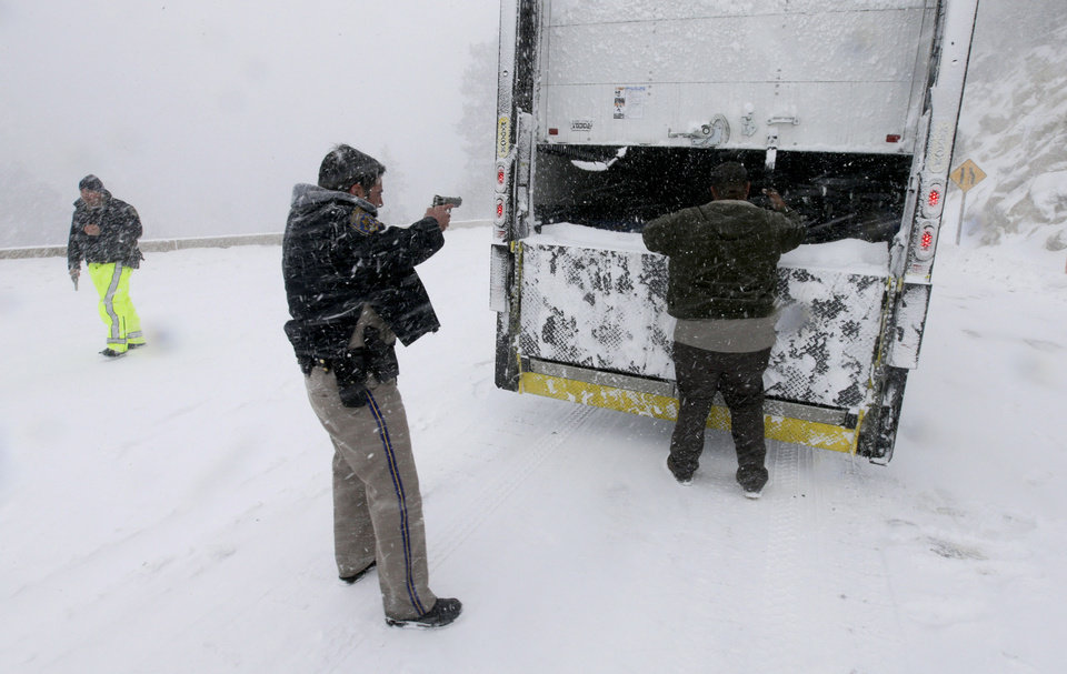 Photo - Members on the California Highway Patrol search a truck for Christopher Dorner, a former Los Angeles police officer accused of carrying out a killing spree because he felt he was unfairly fired from his job, Friday, Feb. 8, 2013, in Big Bear Lake, Calif. (AP Photo/Chris Carlson)