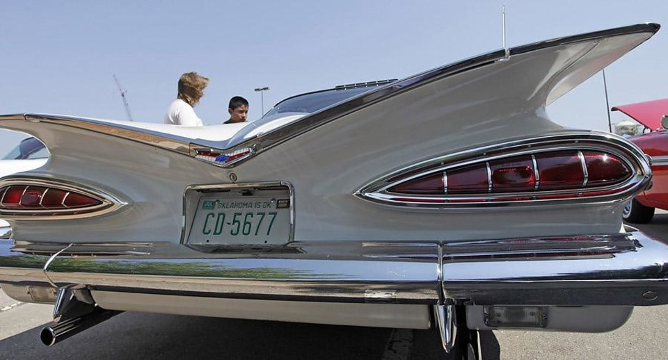 Photo -  Donna and Brandon Krist look at an original, unrestored 1959 Chevy Impala Sport Coupe with 50,000 miles owned by Dennis and Sharon Doughty of Edmond at the LibertyFest Car Show on the campus of UCO Saturday, June 27, 2009. Photo by Doug Hoke, The Oklahoman.