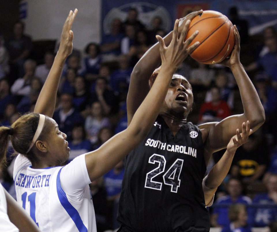 Photo - South Carolina's Aleighsa Welch (24) shoots under pressure from Kentucky's DeNesha Stallworth (11) during the first half of an NCAA college basketball game, Thursday, Feb. 20, 2014, in Lexington, Ky. (AP Photo/James Crisp)