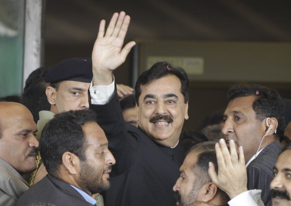 Photo -   Pakistani Prime Minister Yousuf Raza Gilani, center, waves upon his arrival at the Supreme Court for a hearing in Islamabad, Pakistan, Thursday, April 26, 2012. The Supreme Court convicted Gilani of contempt on Thursday for refusing to reopen an old corruption case against President Asif Ali Zardari on Thursday, but spared him a prison term in a case that has stoked political tensions in the country. (AP Photo/B.K. Bangash)
