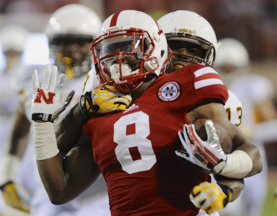 Photo - Wyoming linebacker Devyn Harris, rear, tackles Nebraska running back Ameer Abdullah (8), in the first half of an NCAA college football game in Lincoln, Neb., Saturday, Aug. 31, 2013. (AP Photo/Dave Weaver)