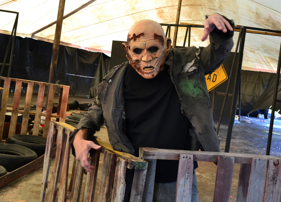 Photo - This undated image provided by Saint LuciferÂ's Haunted Asylum in Flint, Mich., shows a zombie awaiting his fate from paintball-shooting visitors. Saint LuciferÂ's is offering a shoot-the-zombie game, part of a trend in which Halloween attractions are becoming more interactive. Instead of walking through a haunted house as a passive observer, guests are now being invited to partake in challenges and games of various sorts. (AP Photo/ Saint LuciferÂ's Haunted Asylum)  ORG XMIT: NYET314