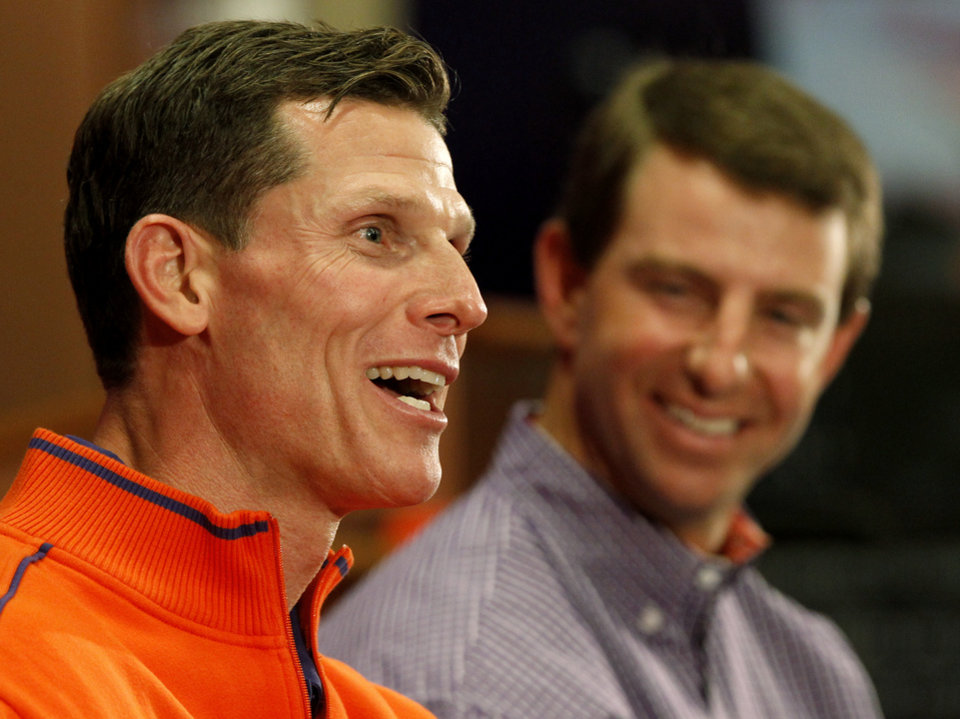 Brent Venables, left, answers a question as head coach Dabo Swinney looks on during an NCAA college football news conference where Venables was introduced as the new defensive coordinator at Clemson, on Friday, Jan. 20, 2012, in Clemson, S.C, (AP Photo/The Independent-Mail, Sefton Ipock) THE GREENVILLE NEWS OUT, SENECA NEWS OUT ORG XMIT: SCAND201