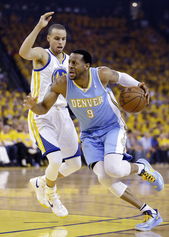 Photo - Denver Nuggets' Andre Iguodala, right, dribbles past Golden State Warriors' Stephen Curry during the first half of Game 6 in a first-round NBA basketball playoff series in Oakland, Calif., Thursday, May 2, 2013. (AP Photo/Ben Margot)