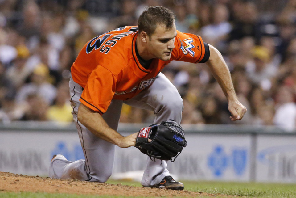 Photo - Miami Marlins relief pitcher Dan Jennings falls to the ground after being hit by a line drive off the bat of Pittsburgh Pirates' Jordy Mercer during the seventh inning of a baseball game in Pittsburgh Thursday, Aug. 7, 2014. Jennings was driven off the field. (AP Photo/Gene J. Puskar)