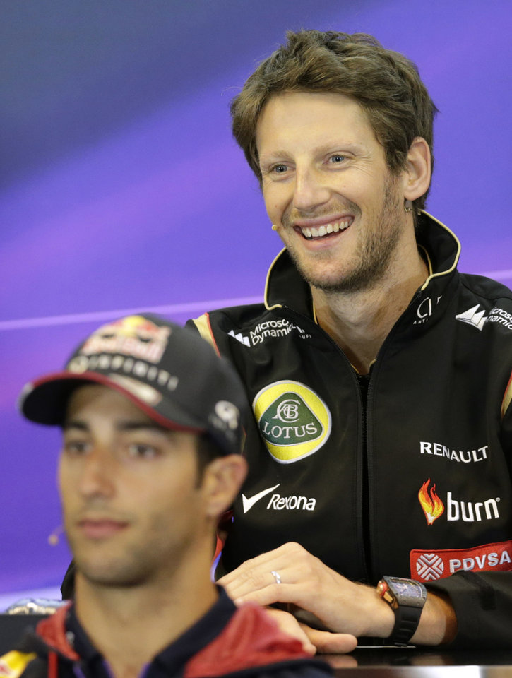 Photo - Lotus driver Romain Grosjean of France, top, smiles as he addresses the media with Red Bull driver Daniel Ricciardo of Australia, ahead of Sunday's Belgian Formula One Grand Prix in Spa-Francorchamps, Belgium, Thursday, Aug. 21, 2014. (AP Photo/Yves Logghe)
