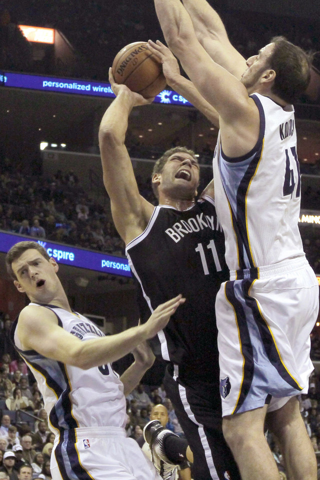 Photo - Brooklyn Nets' Brook Lopez (11) goes to the basket between Memphis Grizzlies' Kosta Koufos (41) and Jon Leuer, left, in the first half of an NBA basketball game in Memphis, Tenn., Saturday, Nov. 30, 2013. (AP Photo/Danny Johnston)