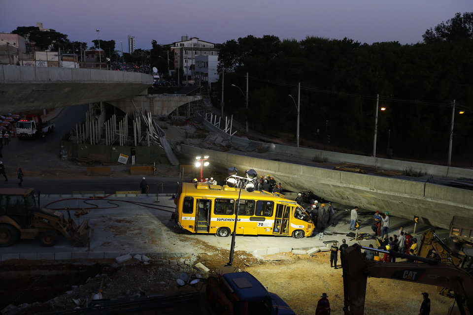 Photo - A bus sits damaged next to a bridge after it collapsed in Belo Horizonte, Brazil, Thursday, July 3, 2014. The overpass under construction collapsed Thursday in the Brazilian World Cup host city. The incident took place on a main avenue, the expansion of which was part of the World Cup infrastructure plan but, like most urban mobility projects related to the Cup, was not finished on time for the event. (AP Photo/Victor R. Caivano)