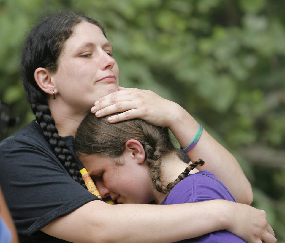 Photo - Tabitha Morgan comforts her daughter Stormie, 11, Monday, June 8, 2009, at a road side memorial, on the one-year anniversary of the murders of Skyla Whitaker and Taylor Placker near Weleetka. Stormie was a friend of the girls. Photo By David McDaniel, The Oklahoman.